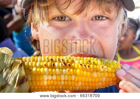 Happy boy eating corn on the cob