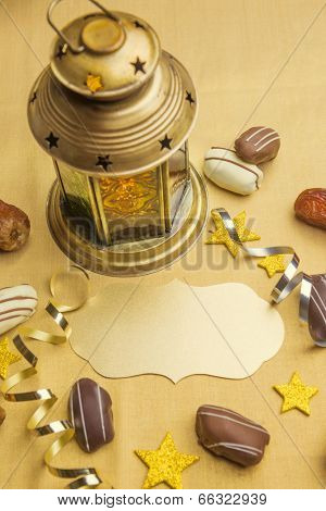 Empty golden plaque with Ramadan lantern and date chocolates