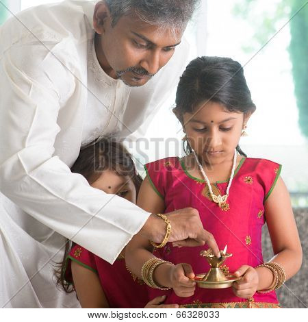 Indian family in traditional dress preparing to celebrate diwali or deepavali at home. Little girl hands holding oil lamp during festival of light.