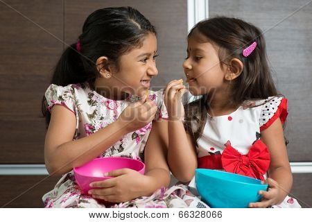 Two cute Indian girls eating murukku. Asian sibling or children living lifestyle at home.