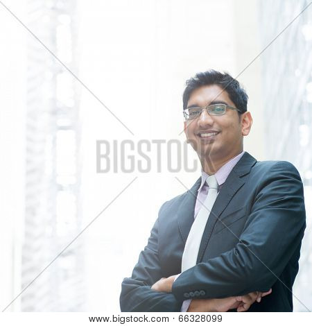 Portrait of a good looking smiling Indian businessman crossed arms standing at modern building, with natural light.
