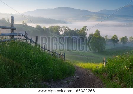 Morning landscape with a road in the mountain village. Sunny morning with fog over the settlement. Carpathian mountains, Ukraine, Europe