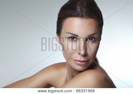 Closeup portrait of 30 years old young woman on light grey studio background