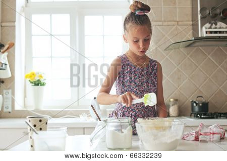 7 years old school girl cooking at the kitchen, casual lifestyle photo series