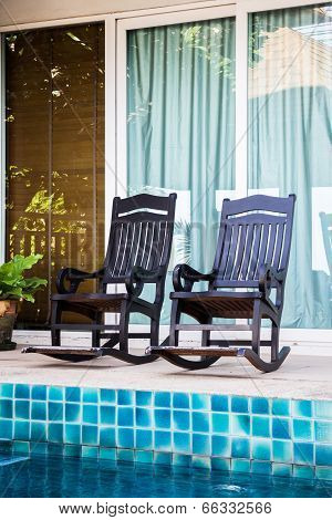 Wooden Arm Chairs Beside The Pool