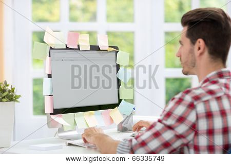 Man looking at a computer monitor with notes on it
