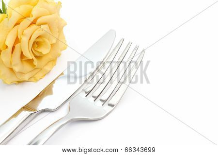 Dinner place setting. Knife and fork with yellow rose on white