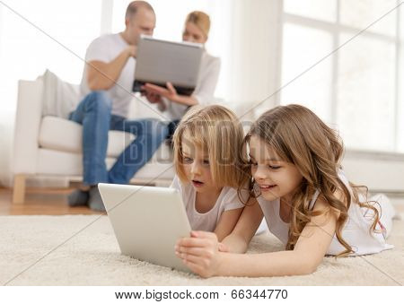 family, children, technology and home concept - smiling sister with tablet pc computer and parents on the back with laptop