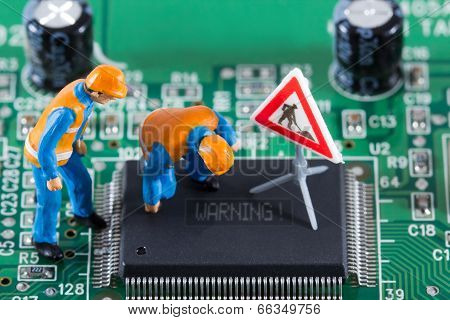 Miniature Engineers Fixing Error On Chip