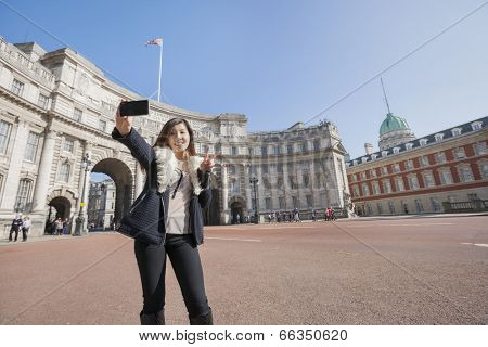 Happy woman taking self portrait against Admiralty Arch in London; England; UK