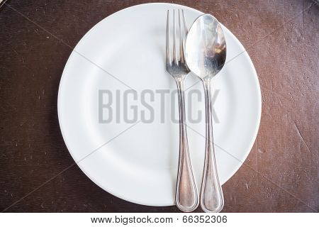 Top View Of White Plate With Spoon And Fork