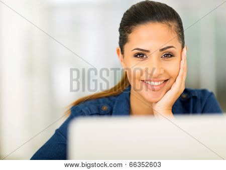 attractive young woman in front of laptop and looking at the camera