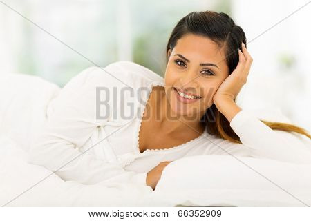 beautiful young woman lying in comfy bed
