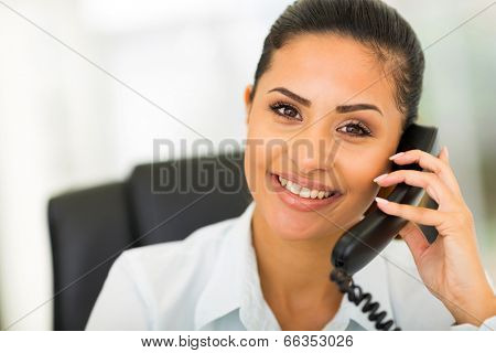 beautiful young businesswoman using landline phone