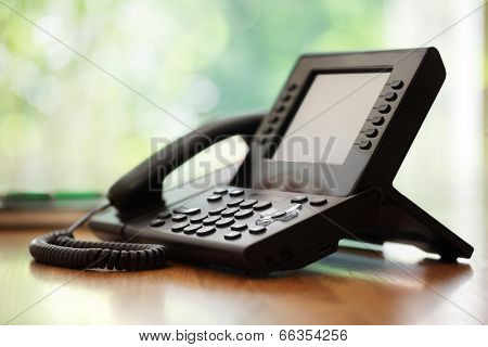 Business telephone with liquid crystal display on a desk in an office