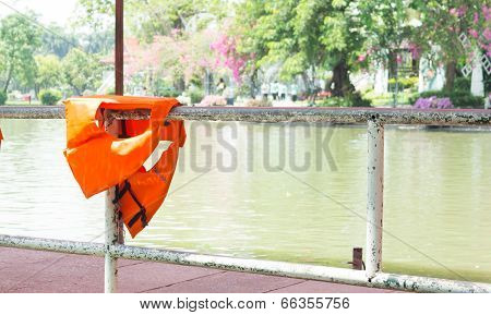 Orange Life Jackets Dried On Fence