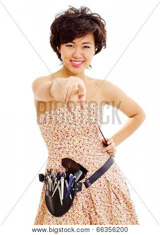 Smiling young asian hairdresser with comb in left hand and professional tools on belt showing forefinger on you, isolated on white background