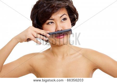 Pretty asian girl posing with comb like with moustache, isolated on white background