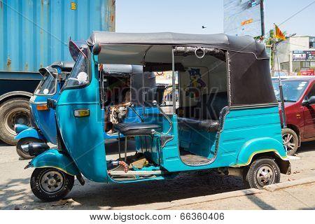 HIKKADUWA, SRI LANKA - FEBRUARY 22, 2014: Blue tuk-tuk vehicle parked on street of Hikkaduwa. Tuk-tuks are very popular way of sightseeing the town.