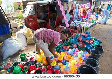 HIKKADUWA, SRI LANKA - FEBRUARY 23, 2014: Local street vendor selling plastic products. The Sunday market is great way to see Hikkaduwa's local life come alive along with local delicacy
