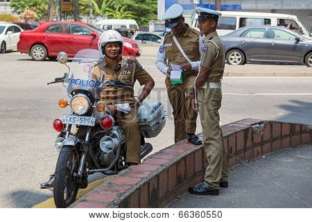COLOMBO, SRI LANKA - FEBRUARY 22, 2014: Group of policemen standing on street. The Sri Lankan police force has a manpower of approximately 85,000.