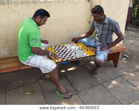 HIKKADUWA, SRI LANKA - FEBRUARY 22, 2014: Local men play checkers on street. Checkers is very popular board game also known as Draughts.
