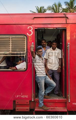 HIKKADUWA, SRI LANKA - FEBRUARY 22, 2014: Local people standing in the train doorway. Taking the train is a great way to get around Sri Lanka, as it's cheap, safe and part of the experience.
