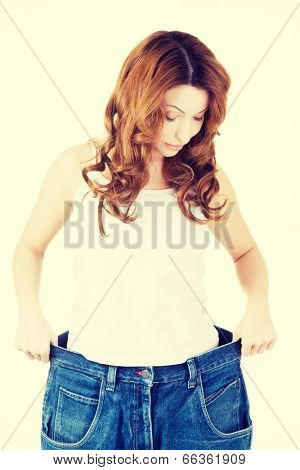 Happy fit woman with big pants, showing how much weight she lost.