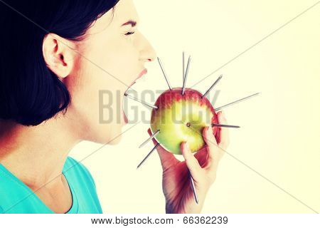 Throat pain concept. Woman eating apple with nails.