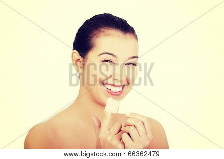 Pretty young woman using adhesive plaster on her injured finger.