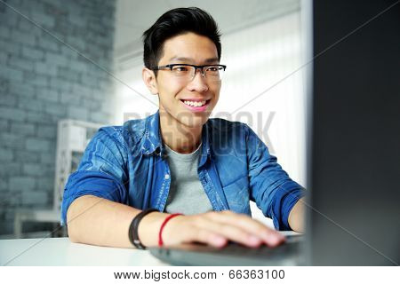 Happy young asian man using laptop
