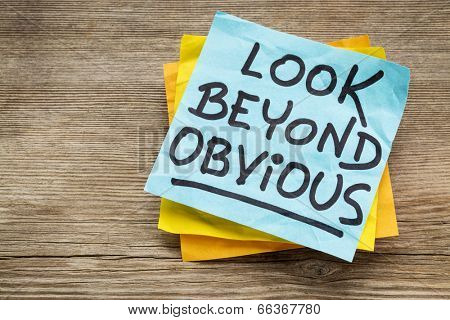 look beyond obvious - creativity and motivation reminder on a sticky note against grained wood