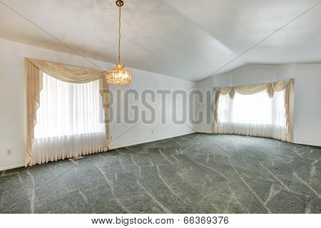 Empty Living Room With Vaulted Ceiling And Green Carpet Floor