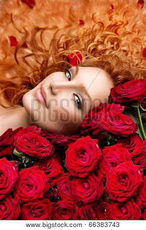 Beauty Fashion Woman with long curly red hair and beautiful red roses bouquet. Hairstyle with flowers. Beauty model girl lying on beautiful roses.  Wavy healthy hair. Permed hair