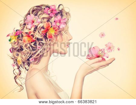 Beauty girl takes beautiful flowers in her hands. Blowing flower. Hairstyle with flowers.  Fantasy g poster