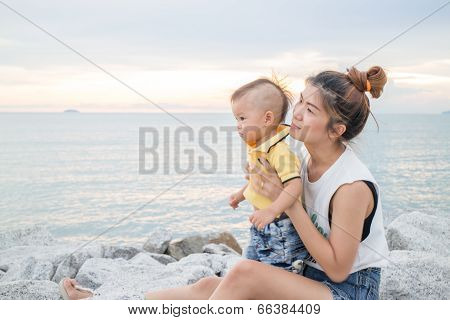 Asian Boy Chilling On The Beach With His Mother