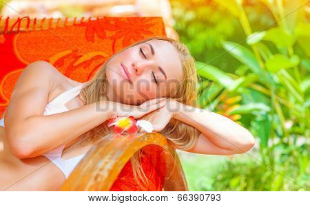 Pretty female on tropical resort, lying down on deckchair with closed eyes and taking sun bath, enjoying exotic nature, summer vacation concept
