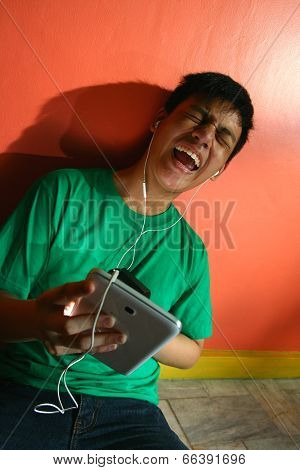 Young asian teen listening to music on a tablet in a living room