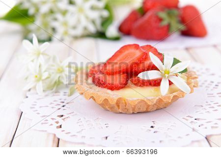 Tasty tartlet with strawberries on table close-up
