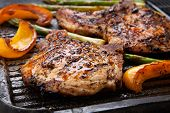picture of pork chop  - Juicy pork chops are grilled on griddle with asparagus and bell pepper - JPG