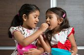 stock photo of child feeding  - Indian girls sharing food - JPG