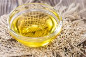 stock photo of sesame seed  - Sesame Oil with some Sesame Seeds on dark wooden table  - JPG