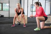 stock photo of jerks  - Young woman lift kettlebells with help of a instructor at fitness gym center - JPG
