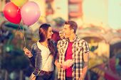 stock photo of candy cotton  - Young smiling couple having a ride on a ferris wheel - JPG
