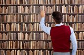 pic of book-shelf  - Young man in library take book from shelf - JPG