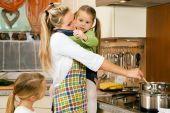 stock photo of homemaker  - Mother with children having a lot of stress doing the homework - JPG