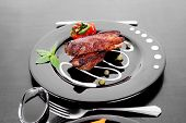 stock photo of red meat  - fresh red beef meat steak barbecue garnished vegetable salad sweet potato and basil on black plate over black wooden table with bbq sauce in sauceboat - JPG