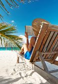 picture of palm-reading  - Young woman reading a book at the beach - JPG