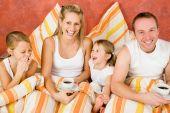 Постер, плакат: Семья из четырех в постели Завтрак