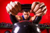 stock photo of kettlebell  - Kettlebell man portrait looking through the handle ring at gym workout - JPG